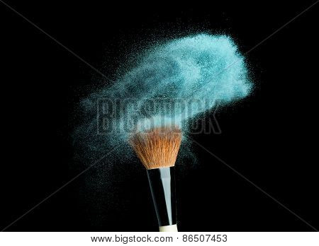 powder brush on black background with blue powder splash
