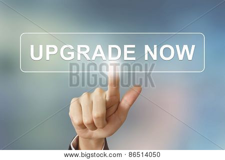 Business Hand Clicking Upgrade Now Button On Blurred Background