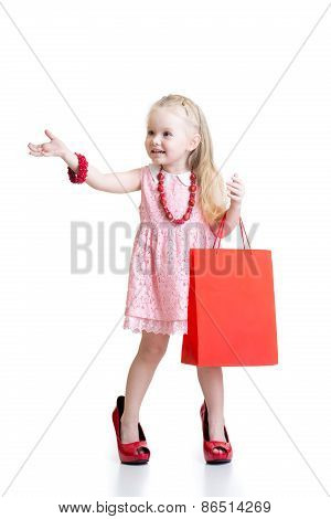 child girl trying her mom's red accessories and shoes on