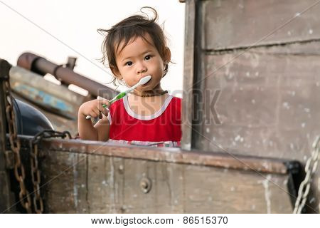 CAN THO, VIETNAM, DECEMBER 12, 2014: A little girl is brushing her teeth on a family boat in the Cai Rang floating market on the Mekong river in Can Tho city, Vietnam.