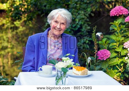 Smiling Old Woman With Snacks At The Garden Table