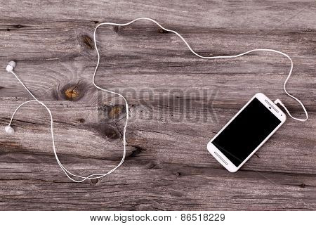 Smart phone with earphones against wooden background