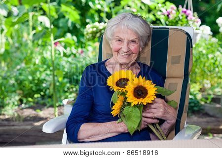 Happy Old Lady Sitting On Chair Holding Sunflowers