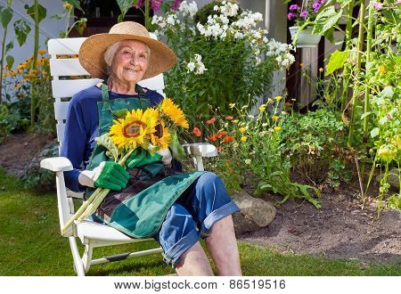 Old Woman Sitting On A Chair Holding Sunflowers