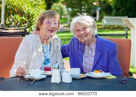 Happy Senior Women Relaxing At The Garden Table