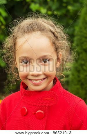 Happy smiling child in red jacket outside