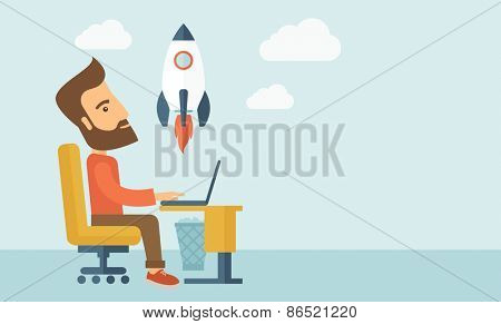 An enthusiastic, eager hipster Caucasian young man with beard sitting in front of his laptop browsing, researching  and planning a metaphor for new business. On-line start up business concept. A