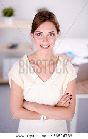 Attractive businesswoman with her arms crossed standing
