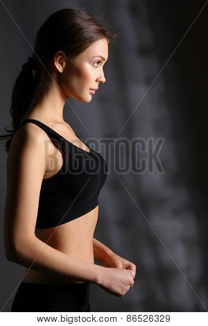 Portrait of a beautiful sports woman on gray background .