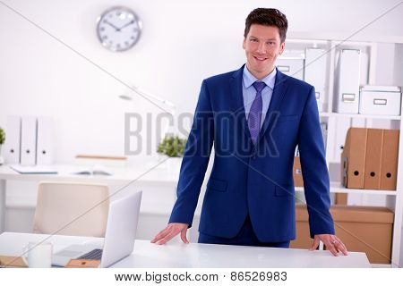Business man or manager standing against his desk at the office.