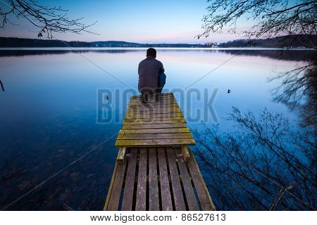 Lake Landscape With Small Wooden Pier And Man Silhouette