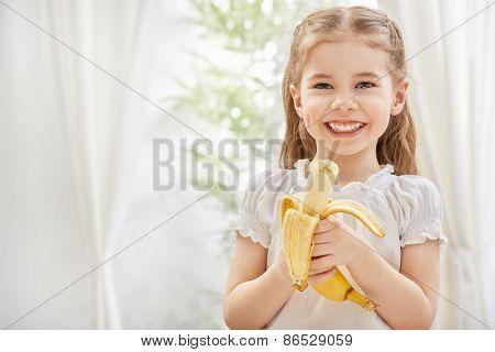 little girl holding yellow banana