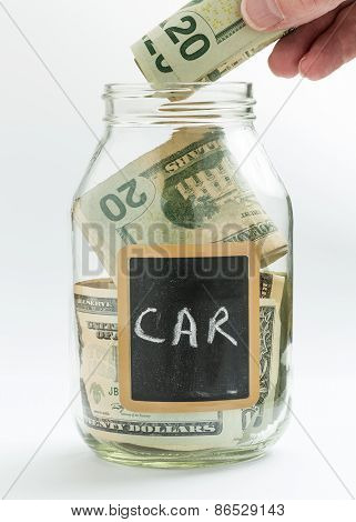Hand Inserting Money Into Saving Jar Or Bank