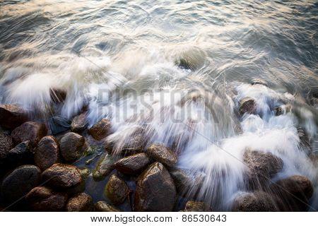 Beautiful granite stones into the sea at sunset