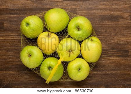 heap of apples in the net bag from the store on wooden