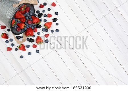 A bucket of berries spilling onto a rustic white kitchen table. High angle shot with the pail in the upper left corner leaving room for your copy.