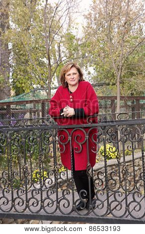 Adult Woman In Red Coat Standing On The Bridge In The Park