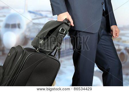 Young Businessman  In  A Modern  Stylish Suit With  Luggage In  The Airport.