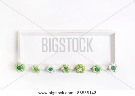 Spring or easter background with handmade flowers on a white wooden shabby chic frame or background.
