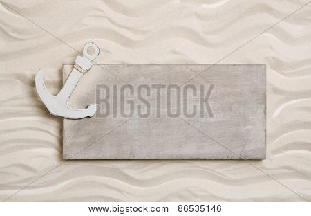White anchor with a wooden sign in the sand. Background for cruising holidays.