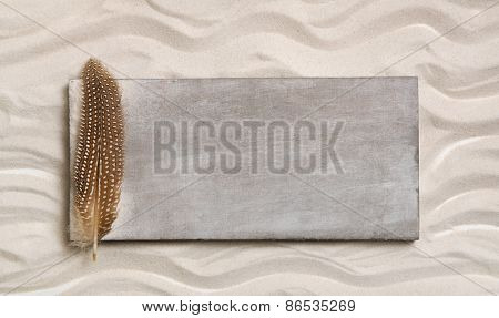 Wooden sign on the beach with sand and a feather.