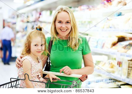 woman and little girl during shopping at fruit vegetable supermarket