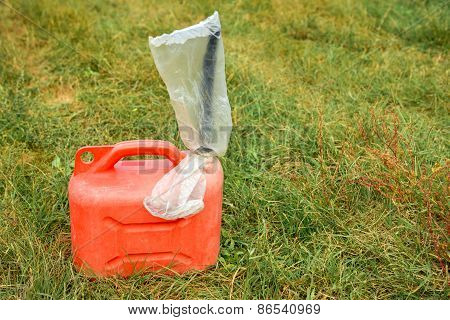 Red jerrycan on green grass