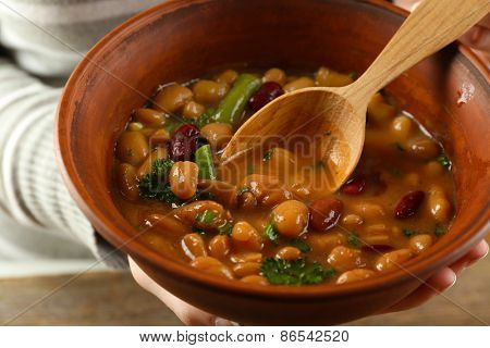 Female hands with beans soup in bowl, close-up