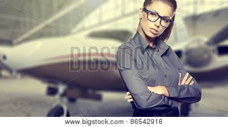 Business woman wearing sunglasses against private jet