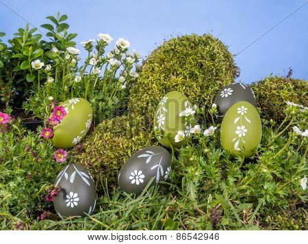 Easter eggs scattered in the grass with fresh spring flowers over blue sky