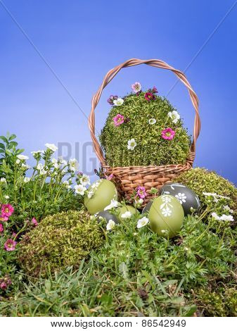 Easter wicker basket with giant moss-grown egg and spring flowers and painted egss in the grass over blue sky