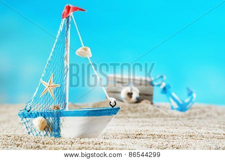 Toy model of ship on sea sand on blue background