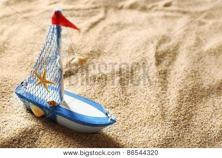 Toy model of ship on sea sand background
