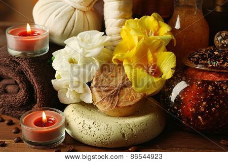 Composition of spa treatment, candle and flowers  on wooden table background