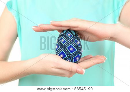 Easter egg in female hands, closeup