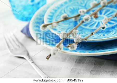 Easter table setting with pussy willow branches on color wooden background
