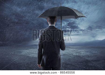 Businessman standing with an umbrella