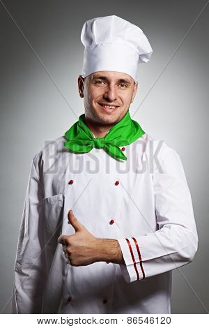 Male chef with thumb up portrait against grey background