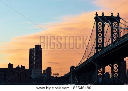 Manhattan Bridge and skyline silhouette view from Brooklyn in New York City at sunset