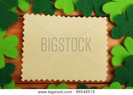 Greeting card for Saint Patrick's Day with shamrocks on wooden planks background