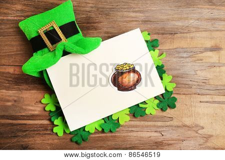 Greeting card for Saint Patrick's Day with leprechaun hat on wooden table background