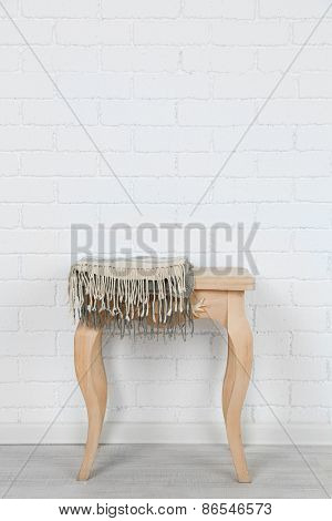 Wooden chair with plaid on white brick wall background