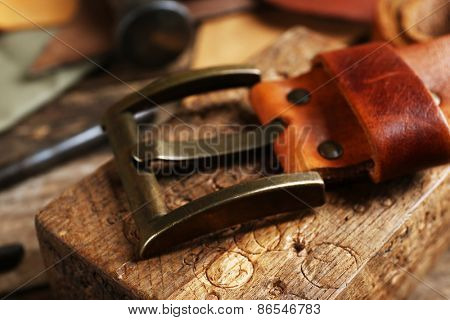 Craft tools with leather belt on table close up