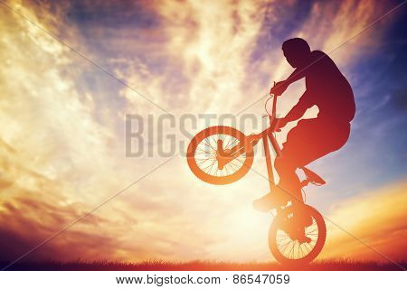 Man riding a bmx bike performing a trick against sunset sky. Extreme sport
