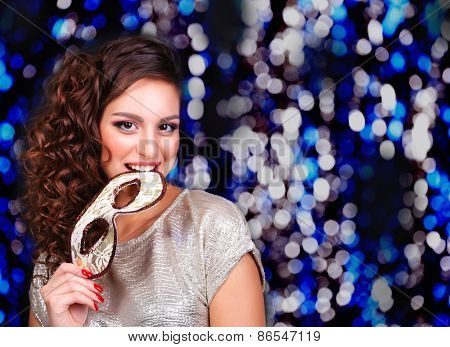 Beautiful girl with masquerade mask on lights background