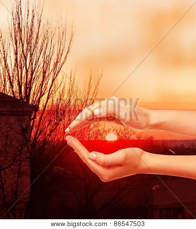 Woman holding sun in hands