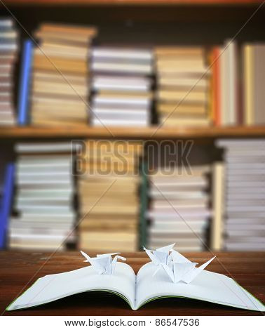 Origami cranes with notebook on bookshelves background