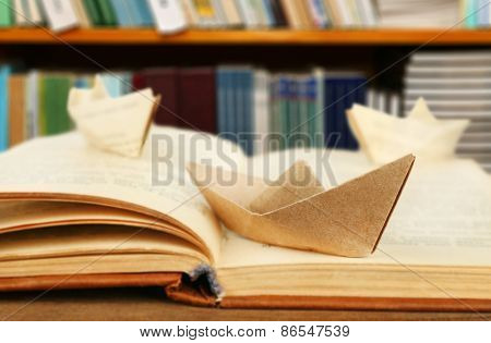 Origami boats with old book on bookshelves background