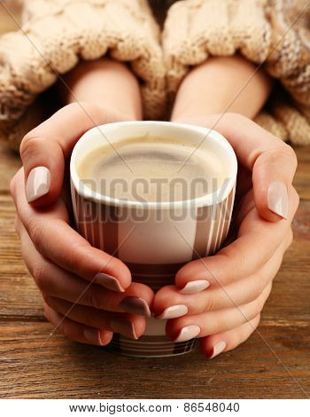 Female hands holding cup of coffee on wooden table close up
