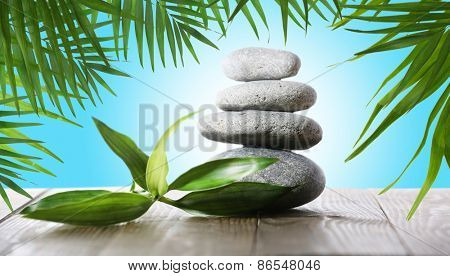 Stack of spa stones with green leaves on blue background